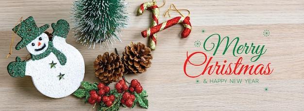 Banner de feliz natal e feliz ano novo para a capa ou capa do site de mídia social ou decoração de página de fã. foto de ornamentos decorativos com texto de bênção de natal e letras com adereços de boneca de show.