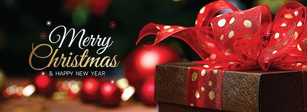 Banner de feliz natal e feliz ano novo para a capa ou capa do site de mídia social ou decoração de página de fã. foto de ornamentos decorativos com texto de bênção de natal e letras com caixa de presente e laço vermelho.