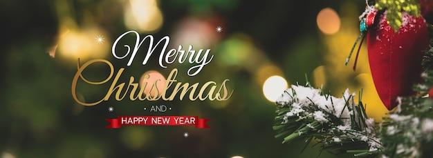 Banner de feliz natal e feliz ano novo para a capa ou capa do site de mídia social ou decoração de página de fã. foto de ornamentos decorativos com texto de bênção de natal e letras com flocos de neve e bokeh.
