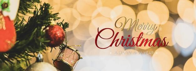 Banner de feliz natal e feliz ano novo para a capa ou capa do site de mídia social ou decoração de página de fã. foto de ornamentos decorativos com texto de bênção de natal e letras com luzes bokeh.
