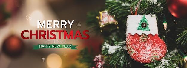 Banner de feliz natal e feliz ano novo para a capa ou capa do site de mídia social ou decoração de página de fã. foto de ornamentos decorativos com texto de bênção de natal e letras com meia vermelha e bokeh.