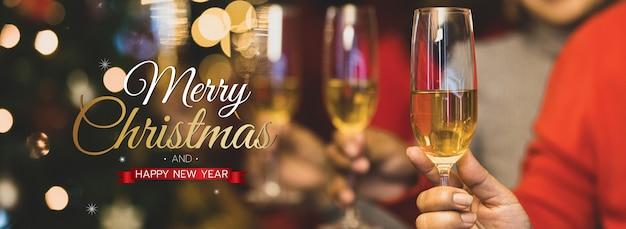 Banner de feliz natal e feliz ano novo para a capa ou capa do site de mídia social ou decoração de página de fã. mãos segurando taças de vinho convidam para comemorar com texto de natal de bênção e luz bokeh.