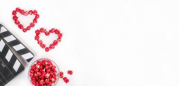 Banner de fundo, conceito de cinema no dia dos namorados. claquete com corações feitos de pipoca de caramelo vermelho com espaço de cópia em um fundo branco.