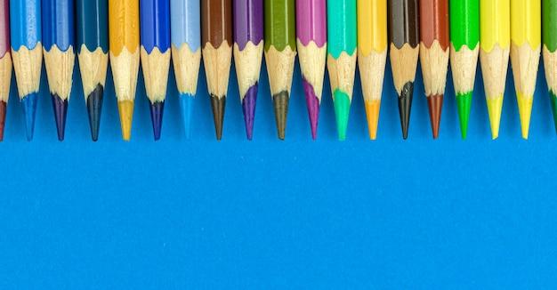 Banner de fundo de borda de lápis de cor com espaço de cópia, foto de vista de topo de mesa de escritório em azul