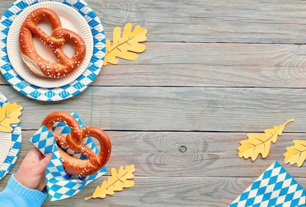 Banner de fundo oktoberfest com espaço de texto, mão segurando o pretzel e decorações brancas azuis