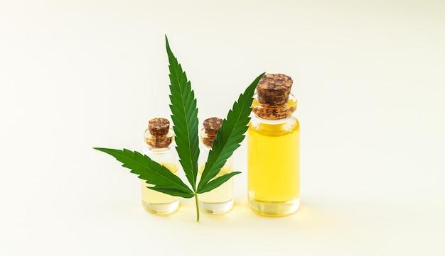 Banner de garrafas de vidro de óleo de cânhamo e close-up de folha de maconha