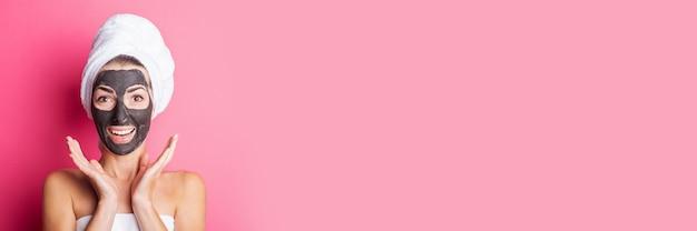 Banner de jovem sorridente surpreso com máscara facial preta em um fundo rosa