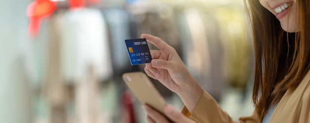 Banner de mulher asiática usando cartão de crédito com celular para fazer compras online
