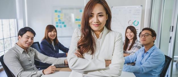 Banner de mulher de negócios asiáticos com braços cruzados e em pé sobre o grupo de colegas