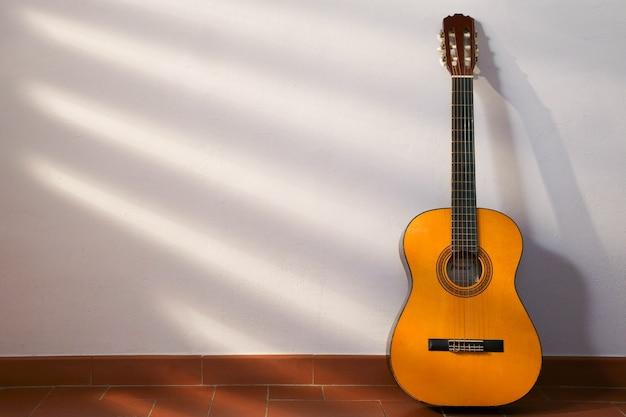 Banner de música com instrumento de guitarra espanhola em madeira com raios de sol e espaço de cópia para texto