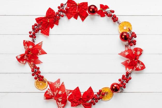 Banner de natal. círculo feito de peças de decoração de natal em um fundo branco de madeira