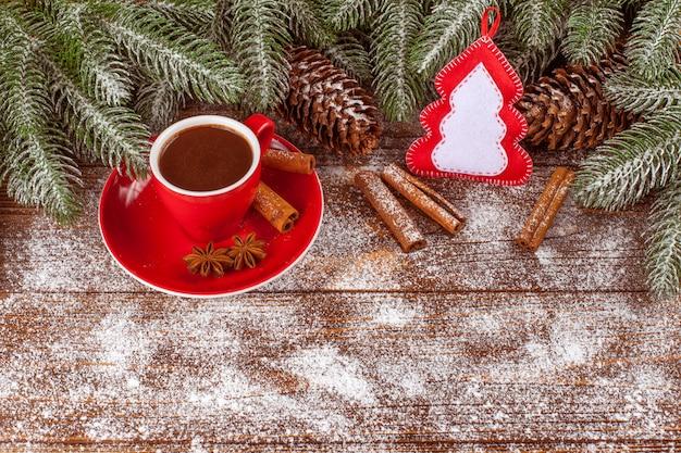 Banner de natal com árvore verde, cones, copo vermelho com chocolate quente, decorações de feltro artesanal