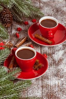Banner de natal com árvore verde, cones, copo vermelho com chocolate quente, decorações vermelhas, canela