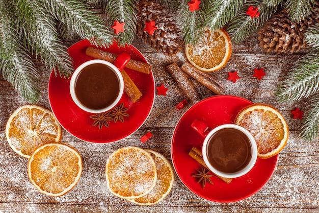 Banner de natal com árvore verde, cones, copos vermelhos com chocolate quente, laranja e canela.