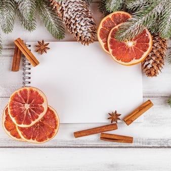 Banner de natal com árvore verde, cones, laranja, canela e notebook