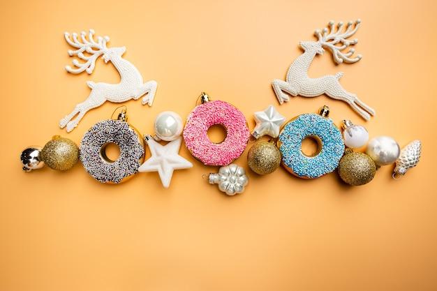 Banner de natal com donut vitrificado de brinquedo e decorações de natal, vista superior, fundo laranja pastel