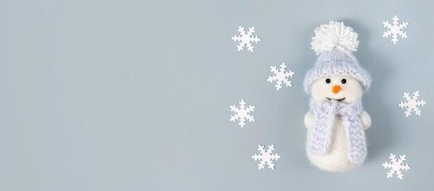 Banner de natal com flocos de neve brancos e um boneco de neve bonito em um fundo azul pastel.