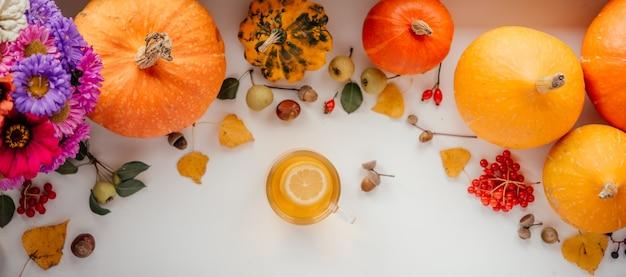 Banner de outono com uma xícara de chá de limão e abóboras