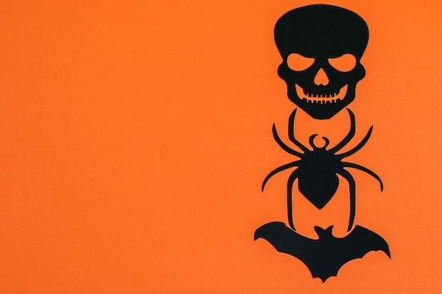 Banner de papel laranja fundo de halloween com aranha preta decorativa e animal morcego espaço vertical para seu texto