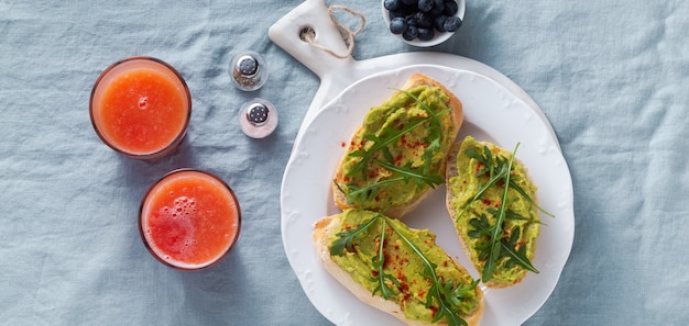 Banner de sanduíche de abacate e rúcula com páprica em cima da mesa. saudável café da manhã ou lanche em um prato numa toalha de mesa de linho azul e suco de laranja espremido na hora