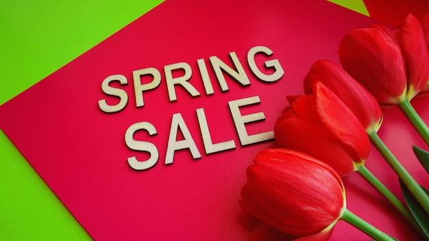 Banner de venda de primavera com tulipas cor de rosa em fundo colorido