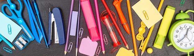 Banner de volta às aulas multicolorido material escolar arco-íris no conselho escolar flatlay copyspace
