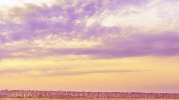 Banner do céu do pôr do sol e nuvens com cores pastel roxas e amarelas paisagem de outono em estilo minimalista