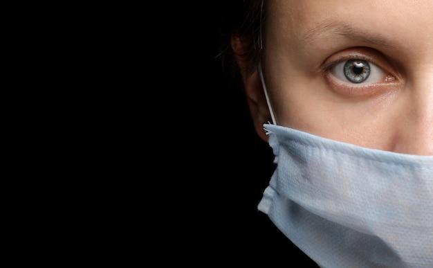 Banner do rosto de uma mulher em uma máscara médica na parede preta, um surto de infecção por coronavírus e proteção contra ela. close-up, retrato de estúdio em um escuro. copie o espaço