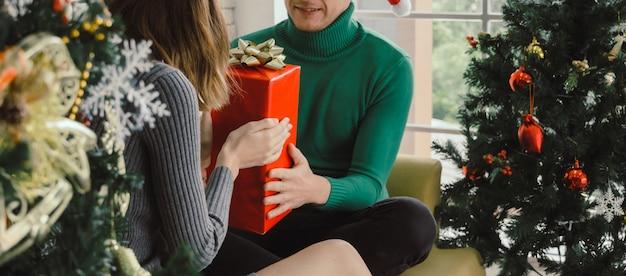 Banner do site. jovem casal homem surpreendente e dando caixa de presente de natal para a namorada com o natal comemorando em casa