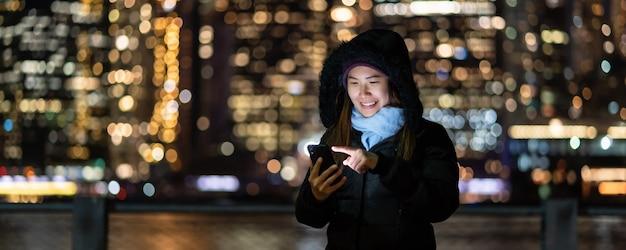 Banner e capa de mulher asiática no inverno terno usando telefone móvel inteligente com ação de sorriso