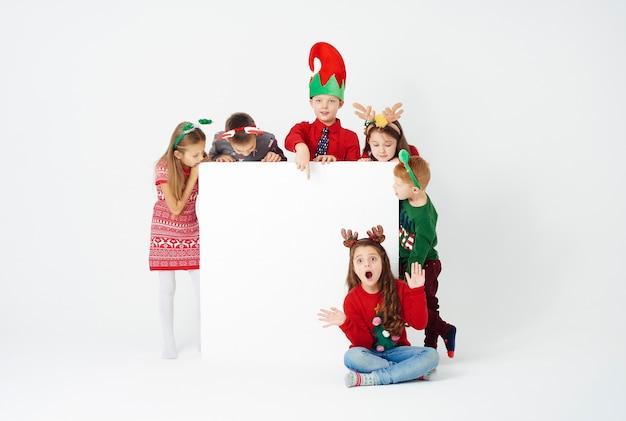 Banner e grupo de crianças fantasiados de natal