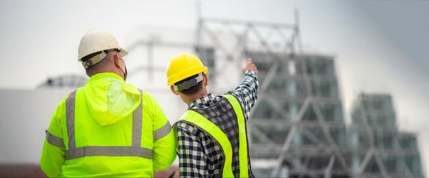 Banner: engenheiro civil e construtores civis inspecionam a estrutura e os planos do canteiro de obras. engenheiro civil e construtores civis fiscalizam o canteiro de obras. engenheiro civil inspeciona o prédio.