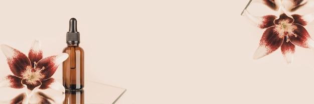 Banner feito com frasco conta-gotas de vidro marrom e lindas flores no espelho, fundo bege. conceito de cosmético spa orgânico natural. vista frontal copie o espaço.