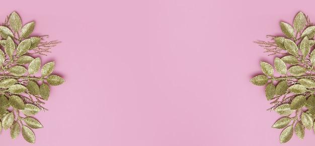 Banner floral com ramos dourados em um espaço de cópia de mesa rosa
