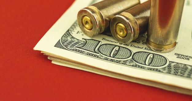 Banner ilegal de comércio de munições, venda de armas, conceito de financiamento do terrorismo, nota de dólar ud e bala no fundo