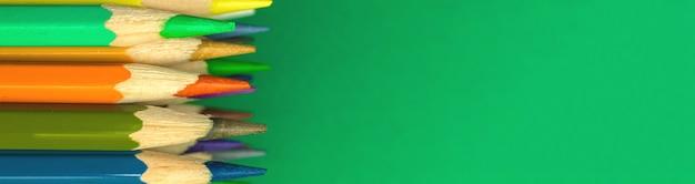 Banner liso escolar com cores e lápis afiados em uma área de trabalho verde, espaço de cópia, conceito de material escolar, foto do espaço de cópia