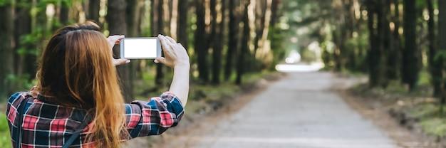 Banner, maquete smartphone nas mãos, meninas na floresta, num contexto de árvores.