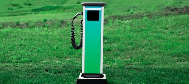 Banner panorâmico do ev, carregador de carro elétrico na grama verde
