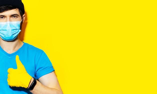 Banner panorâmico, retrato de jovem mostrando os polegares. usando smartwatch, luvas de segurança e máscara médica, proteção contra coronavírus. prevenção de covid-19. fundo de estúdio de amarelo.