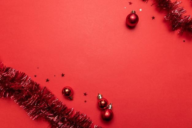 Banner plana moderna com bolas vermelhas, estrelas de brilhos brilhantes e decoração de natal em um vermelho com.