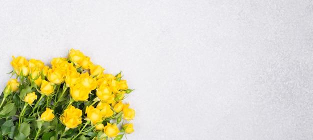 Banner primavera verão conceito com flores rosas amarelas na mesa branca fundo vista superior espaço livre cópia espaço