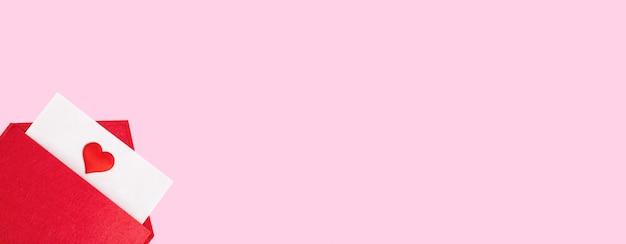 Banner vermelho envelope aberto com uma folha de papel com um coração em um fundo rosa com copyspace. conceito de férias do dia dos namorados e notas de amor