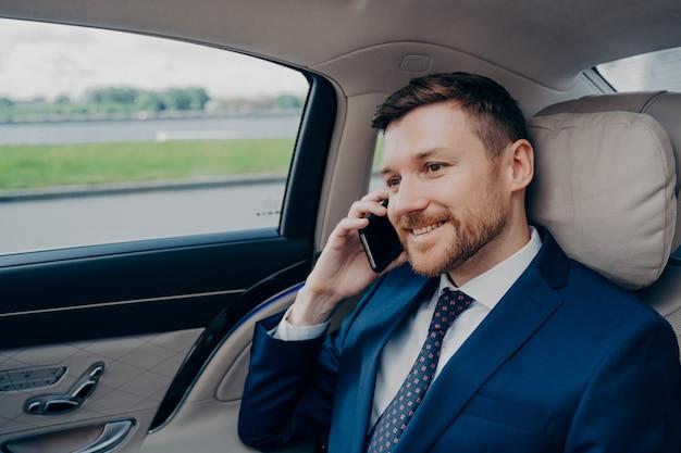 Banqueiro atraente em terno formal, andando em um caro carro corporativo alto com motorista, enquanto fala em seu celular com membros do conselho do banco sobre mudanças financeiras e futura fusão da empresa