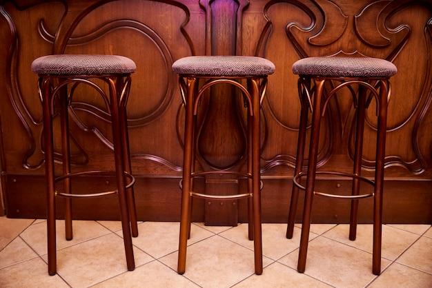 Banquetas de bar de madeira alta estão perto do balcão do bar.