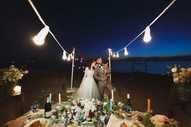 Banquete de casamento na costa do oceano à noite. o noivo está tocando saxofone.
