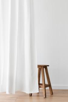 Banquinho de madeira atrás de uma cortina branca