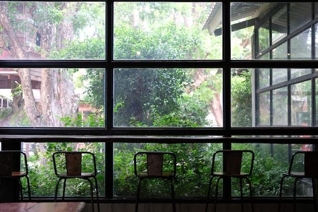 Banquinho no café café perto da janela do jardim