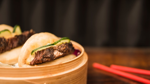 Bao bun cozido no vapor sanduãche em cesta steamer com pauzinhos na mesa de madeira