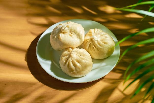 Baozi com recheios variados (de vaca ou de porco) em prato branco. receita e culinária chinesa. pão chinês de carne cozido
