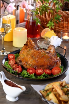 Baqueta de peru assada em uma bandeja de vegetais em uma mesa de jantar festiva em homenagem ao dia de ação de graças.